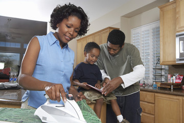 African American woman ironing clothes while man assisting son in homework