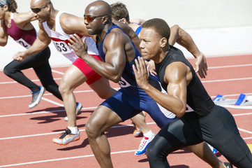 Side view of multiethnic male athletics sprinting on running track