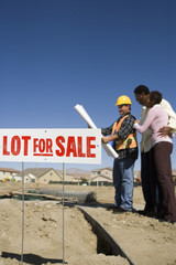 Signboard of lot for sale with couple and construction worker in background