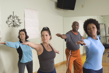 Multi ethnic people practicing stretching exercise in Yoga Class