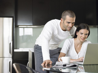 Happy young couple using laptop at dining table in modern kitchen