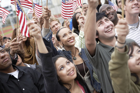 Group of multiethnic people holding up American flags