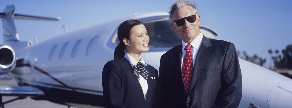 Portrait of senior businessman standing with beautiful stewardess in front of an aircraft