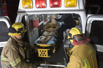 Fire workers in uniform looking at patient and EMT doctor in the ambulance