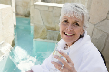Portrait of a happy senior woman enjoying her drink by pool