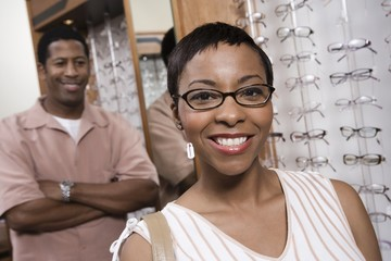 Portrait of happy African American woman wearing glasses with man standing in the background