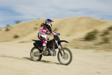 Female off road biker riding the motor bike with speed on a race track
