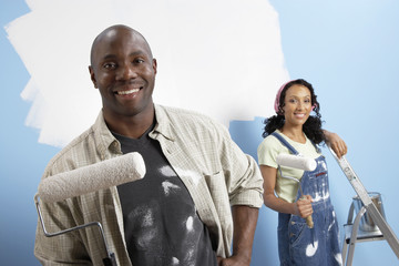 Portrait of a happy African American man with woman painting new house