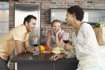 Cheerful multiethnic friends enjoying drinks at kitchen counter