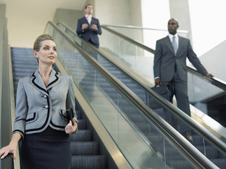 Businesswoman looking away while moving down on escalator with coworkers in background