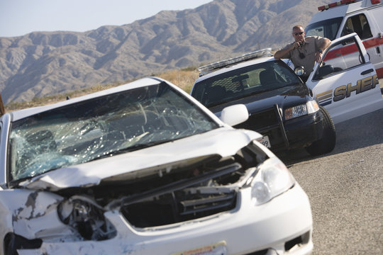 Police officer using radio in front of a damaged car on desert road