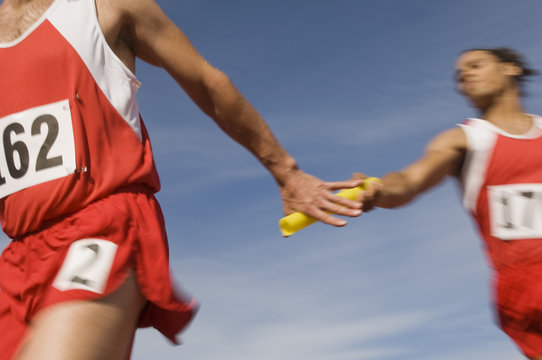 Male athletes passing baton in relay race