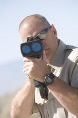 Mature traffic officer looking through radar gun