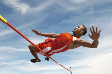 Low angle view of a male high jumper in midair over bar against the sky