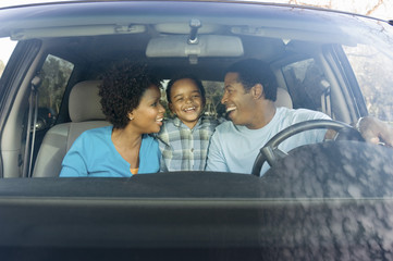 Cheerful African American family sitting in car