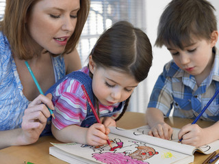 Cute children coloring book while mother assisting them at home