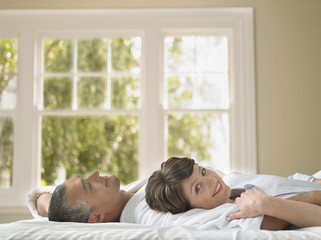 Portrait of happy woman lying with husband in bed