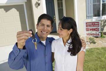 Portrait of Hispanic man with arm around woman holding keys of their new house