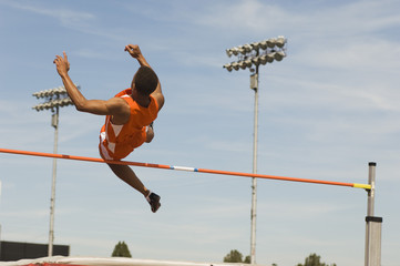 Male athlete performing high jump against sky