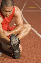 Mature male athlete stretching on racetrack