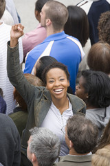 High angle view of a happy African American woman raising hands with people standing around