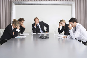 Group of serious business people on conference call in boardroom