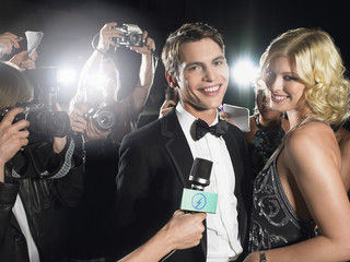 Portrait of young glamorous couple surrounded by paparazzi