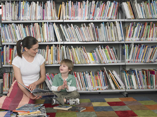 Young woman reading story book to boy in library