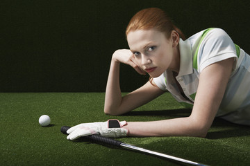 Portrait of serious young woman lying on course with golf club and ball