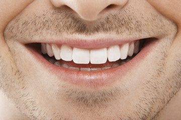 Detailed image of young man smiling with perfect white teeth