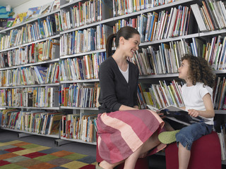 Young girl with teaching reading story book in library