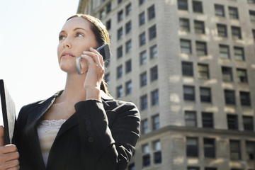 Young businesswoman using mobile phone against office building