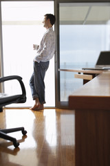 Full length of young businessman having coffee while leaning on sliding door