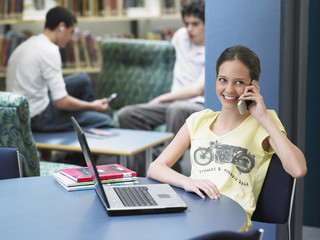 Happy teenage girl using cellphone with laptop on table in library