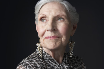 Closeup of a senior woman with pearl earrings looking up against black background
