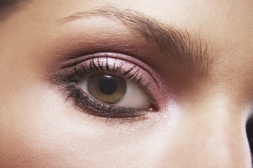 Full frame image of woman's eye with pink eyeshadow