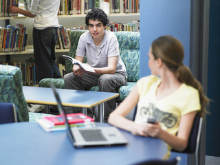 Teenage boy with book looking at girl sitting in library