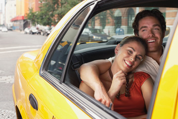 Young couple in yellow taxi on urban street