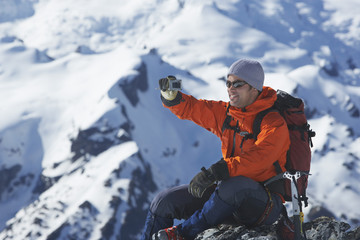 Side view of a male climber taking picture of snowy mountains