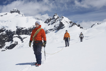 Three male hikers joined by safety line on snowy mountains