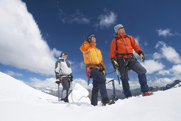 Three male mountain climbers reaching snowy peak against clouds