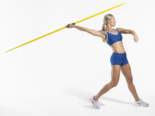 Full length side view of a female athlete preparing to throw javelin against white background