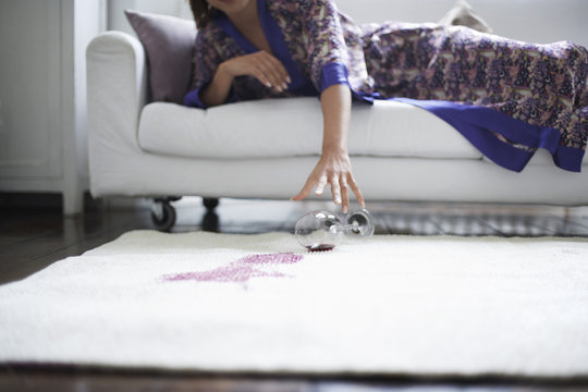 Midsection of woman reaching toward spilled wine glass on rug