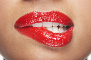 Closeup of sensuous woman biting red lips