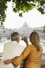 Rear view of couple on bridge photographing cathedral in Rome, Italy