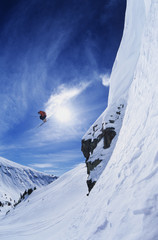 Low angle view of skier jumping from mountain ledge against sky