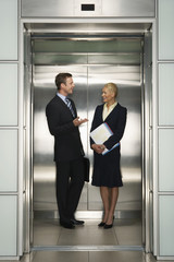 Happy business colleagues communicating in elevator