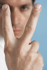 Closeup of a serious man gesturing peace sign against blue background