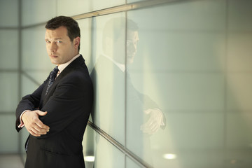 Portrait of confident middle aged businessman with arms crossed leaning on glass wall in office