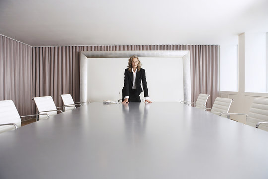 Female business executive standing alone in boardroom